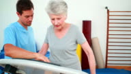 Physical therapist showing patient how to use exercise machine video