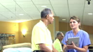 Physical therapist with digital tablet talks to patient video