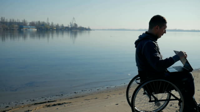physically disabled man sits in a wheelchair at seashore, in hands laptop video