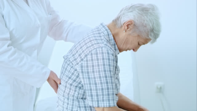 Physician checking the patients spine for irregularities video