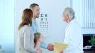 Physician greeting the girl coming for check up with parents video