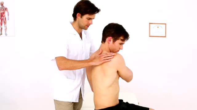 Physiotherapist checking patients injured shoulder and smiling at camera video
