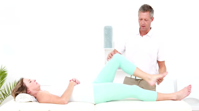 Physiotherapist doing leg stretching to his patient video