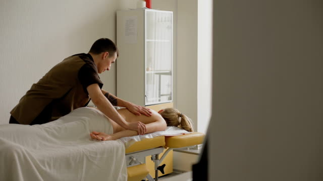 Physiotherapist doing neck massage to his patient in medical office video