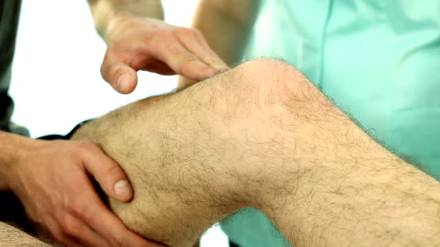 Physiotherapist examining patient knee video video
