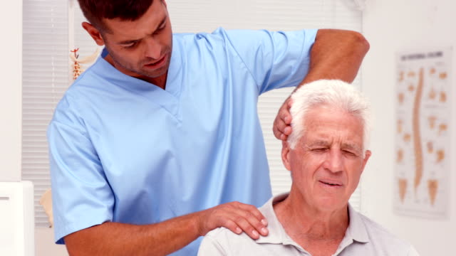 Physiotherapist examining shoulders of patient video