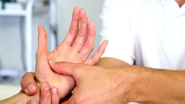 Physiotherapist giving hand massage to a woman video