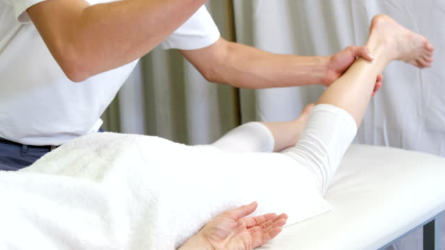 Physiotherapist giving hip massage to a woman video