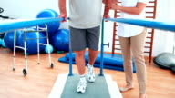 Physiotherapist helping patient walk with parallel bars video