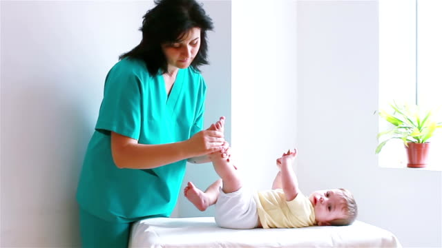 Physiotherapist massaging little baby boy foot video