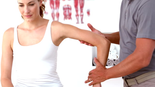Physiotherapist moving patients arm video