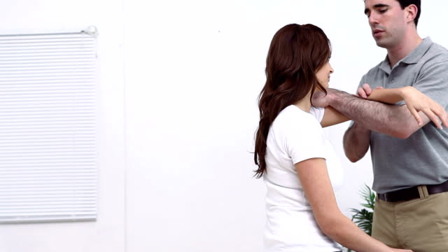 Physiotherapist stretching the arm of his patient video