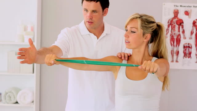 Physiotherapist using a resitance band with his patient video