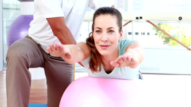 Physiotherapist using exercise ball with patient video