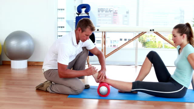 Physiotherapist using foam roller with patient video