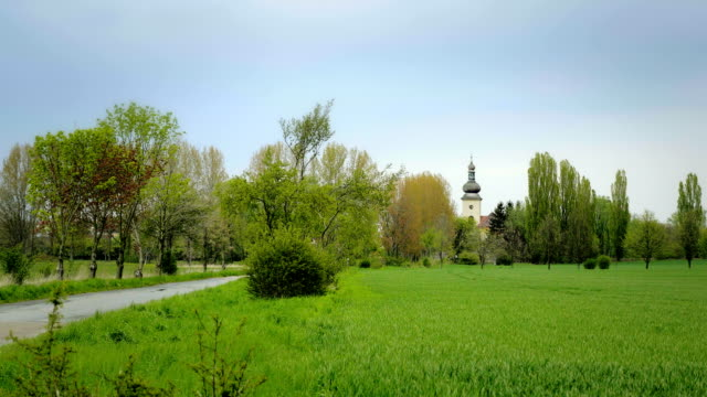 Picturesque landscape with chapel in background and golden wheat field. video