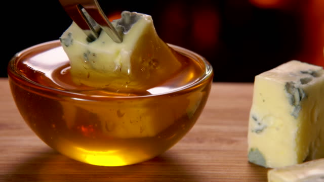 A piece of cheese with blue mold is dipped in a bowl with honey video