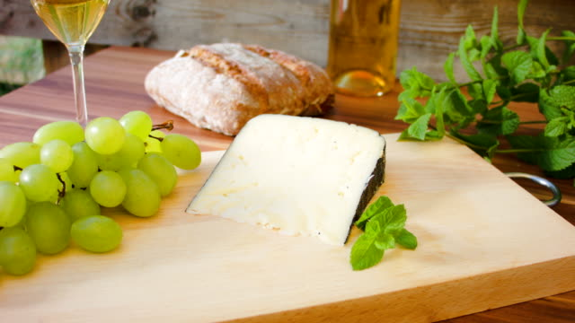 piece of hard cheese on a wooden board with grapes video