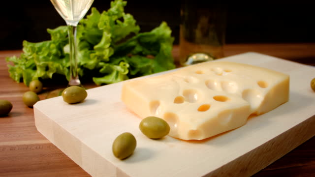 Piece of Maasdam cheese on a wooden board video