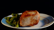 Piece of pork baked with vegetables put on a plate video