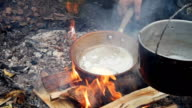 Pieces of butter in the hot pan top view in outdoor video