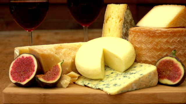 Pieces of cheese and figs on a wooden table video