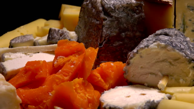 Pieces of french cheese on a black table. video