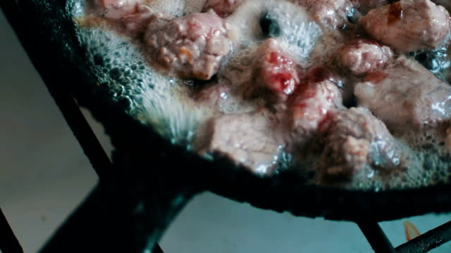Pieces of meat with blood and spices are fried in a pan video