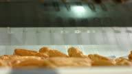Pile of eclairs on conveyor. video