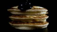A pile of three pancakes with jam. Slow motion video