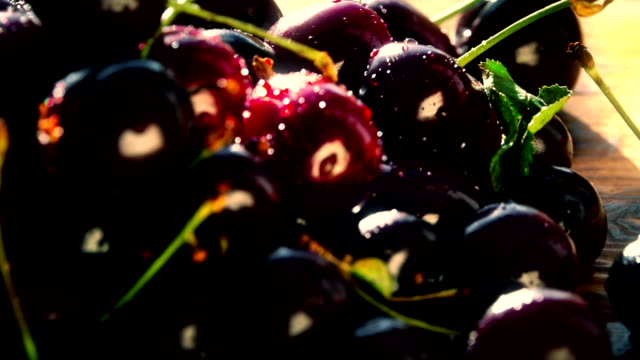 Pile of wet sweet cherries on a wooden table on a sunny day video