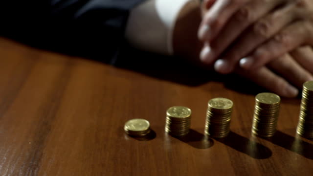 Piles of coins and sandglass on table, depositor earning interest on savings video