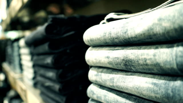 Piles of new jeans in the store pan close up video video