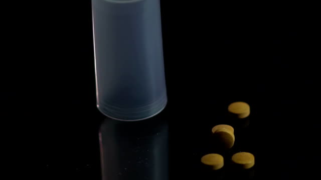 Pill bottle falling on black surface, patient dropping ineffective medicine video