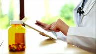 Pill bottle on desk with doctor using digital tablet in medical clinic video