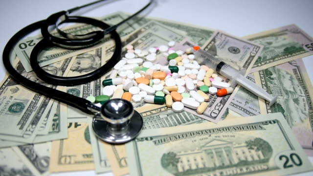 Pills and capsules on dollars, with stethoscope and syringe. Health care costs concept. Slow motion. video