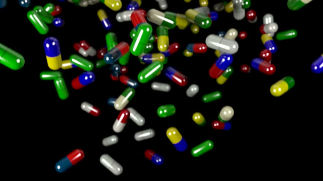 Pills drugs capsules falling slow motion closeup DOF video