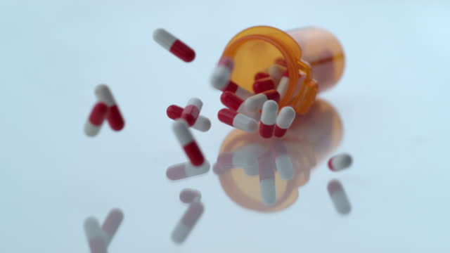 Pills spilling out of bottle in slow motion video