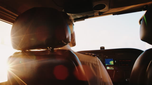 Pilot Flying Small Airplane at Sunrise. POV Cockpit View video