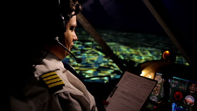 Pilot reading and filling out flight form, navigating plane in autopilot mode video