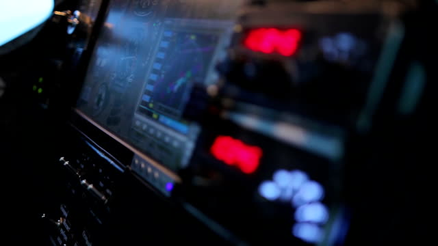 Pilot searching radio frequency on flight panel of airliner, technology video