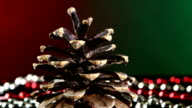 Pine cone for Christmas or New Year and beads, rotation, on red and green, close up video