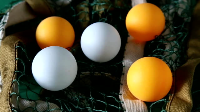 Ping pong balls and green net on rotating table close up. video
