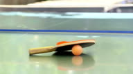 Ping pong racket with a ball on the tennis table outdoor close-up video
