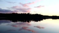 Pink clouds on sunset background, forest lake in Karelia video