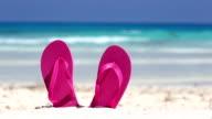 Pink flip flops on white sandy beach near sea waves, nobody video
