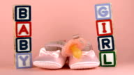 Pink soother falling in front of baby shoes and blocks video