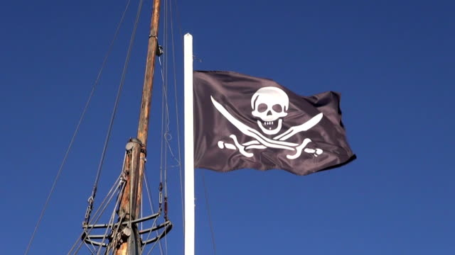 Pirate flag with a skull and bones waving in wind video