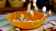 Pistachio nuts falling into bowl, slow motion video