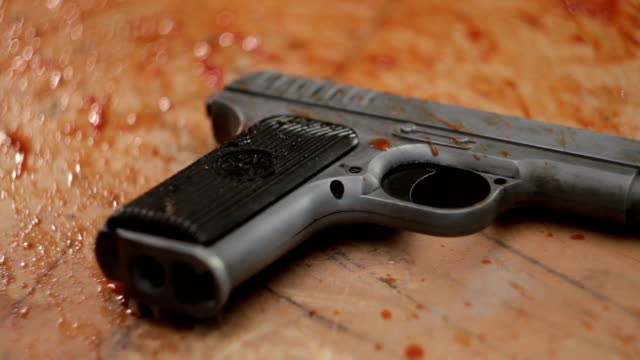 Pistol in blood close-up video